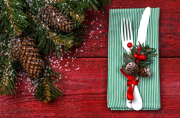 Сервировка рождественского стола с зеленой салфеткой, белой вилкой и ножом, украшенной веточкой омелы и рождественскими сосновыми ветками. рождественские праздники фон.