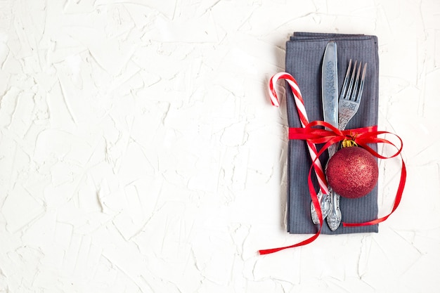Christmas table place setting with knife, fork, red ball, candy cane and ribbon over white table with copyspace
