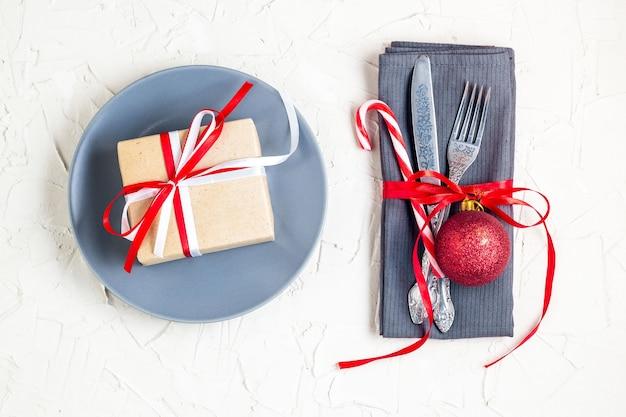 ナプキン、フォーク、ナイフ、ボール、プレート、キャンディケイン、ギフトを備えたクリスマステーブルの場所の設定。クリスマス休暇の背景。フラットレイ、上面図、コピースペース