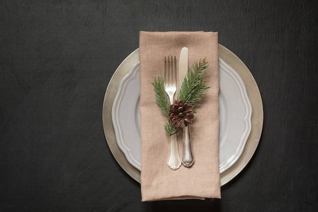 Christmas table place setting with silverware and dark natural evergreen decor.