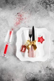 四角いプレート、お祝いの装飾が施されたカトラリーとクリスマステーブルの場所の設定