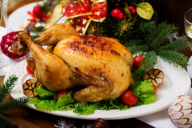 Christmas table served with a turkey, decorated with bright tinsel and candles