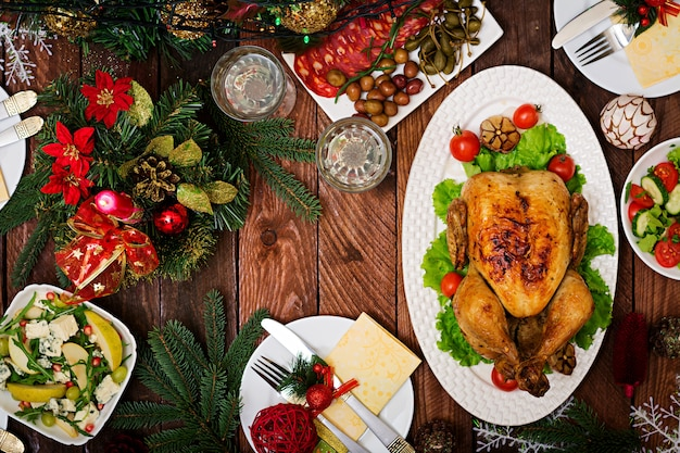 Christmas table served with a turkey, decorated with bright tinsel and candles.
