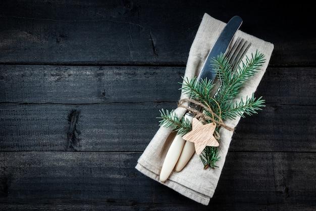 Сервировка рождественского стола - винтажные столовые приборы на льняной салфетке и черном деревянном фоне, свободное место для вашего текста.