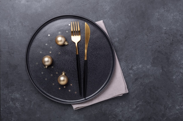 Christmas table setting. black ceramic plate with golden balls and cutlery on stone background. gold decoration - image