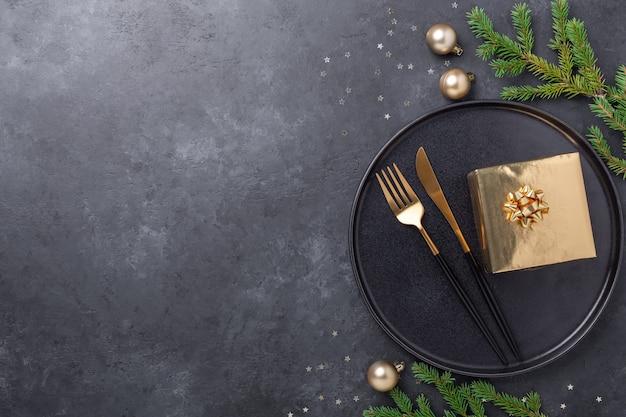 Сервировка рождественского стола. черная керамическая тарелка с золотой подарочной коробкой, еловой веткой и аксессуарами на каменном фоне. золотое украшение - image