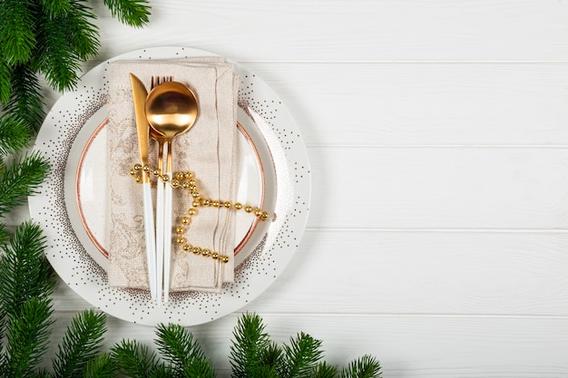 Christmas table setting concept on white wooden background. plate, napkin and golden cutlery and christmas decorations on white background top view, free space for text. high quality photo
