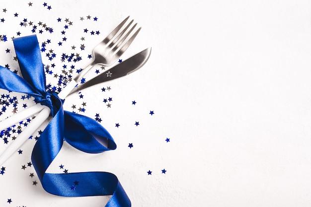 幻の青いリボンと白い背景の上の星の紙吹雪で飾られたクリスマステーブルの設定。