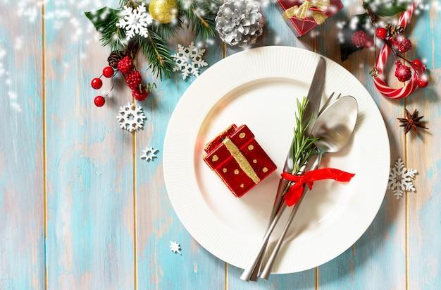 クリスマステーブルの設定お祝いのプレートとお祝いのテーブルに装飾が施されたカトラリー上面図フラットレイ