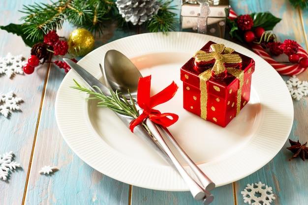 クリスマスのテーブルセッティングお祝いのプレートとお祝いのテーブルに装飾が施されたカトラリー