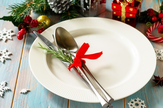Christmas table setting festive plate and cutlery with decor on festive table