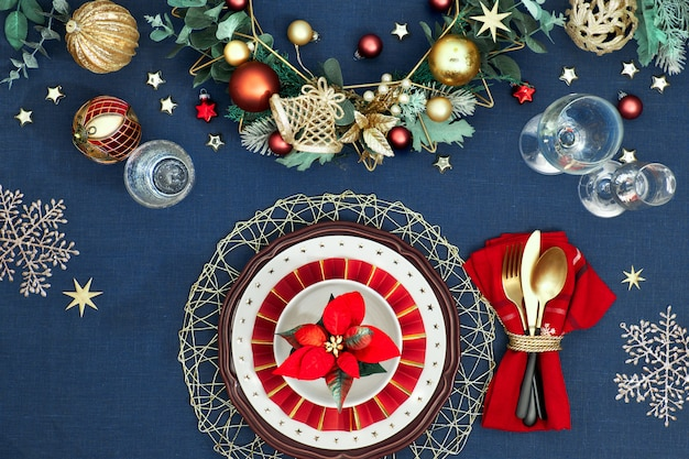 Christmas table setting in gold, burgundy and classic blue colors. flat lay, top view on decorative table layout, golden cutlery. traditional xmas decor on classic blue linen