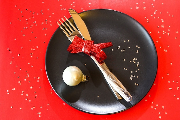 빨간색 테이블 크리스마스 디너 파티에 흰색 공이 있는 검은색 접시에 크리스마스 테이블 설정