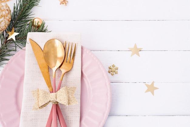 ホワイトピンクゴールドカラーのクリスマステーブルセッティング。ピンクのプレート、金の弓が付いたカトラリー、モミの枝、雪片、星。