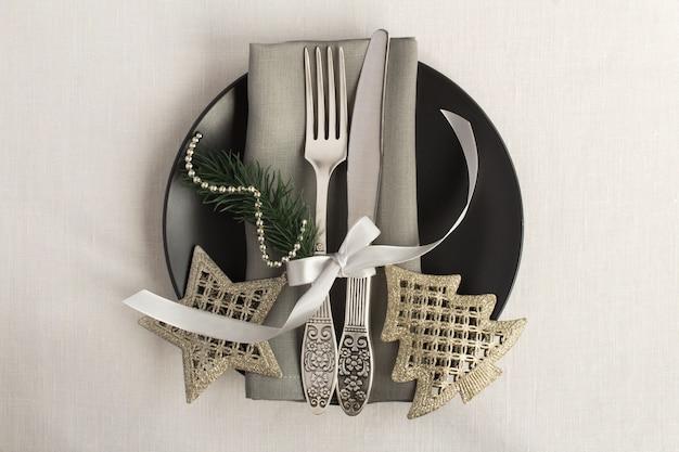 黒い板にクリスマステーブルの設定、白い繊維の表面。上面図。スペースをコピーします。