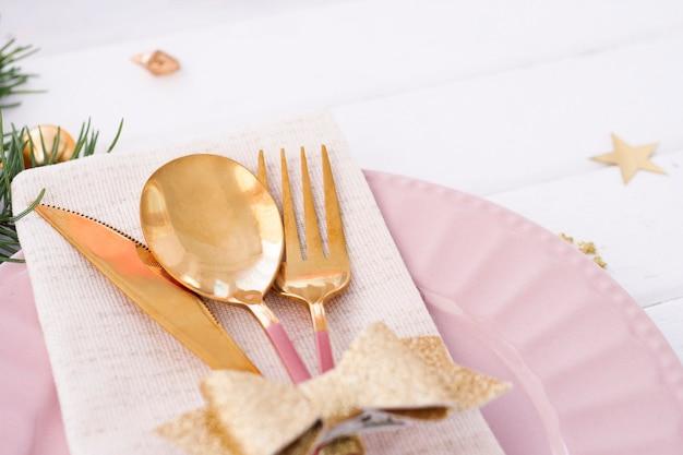 クリスマステーブルの設定。ピンクのプレート、金の弓が付いたカトラリー、モミの枝と星。