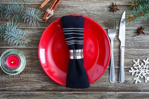 Сервировка рождественского стола. красная тарелка, вилка, нож, ветка елки на деревянном фоне. рождество рождество новый год праздник фон.