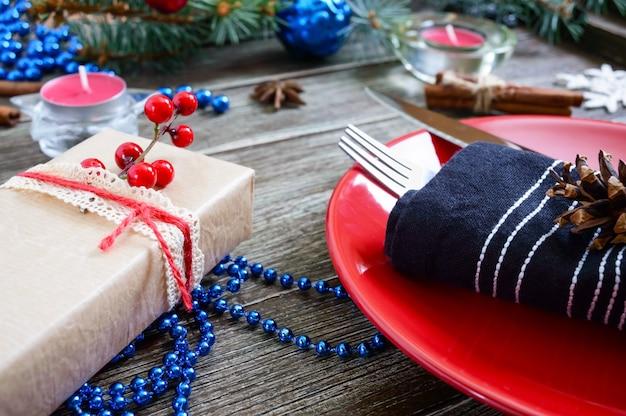 Сервировка рождественского стола. красная тарелка, вилка, нож, свеча, салфетка, ветка подарков елки на деревянном фоне. рождество рождество новый год праздничная открытка.