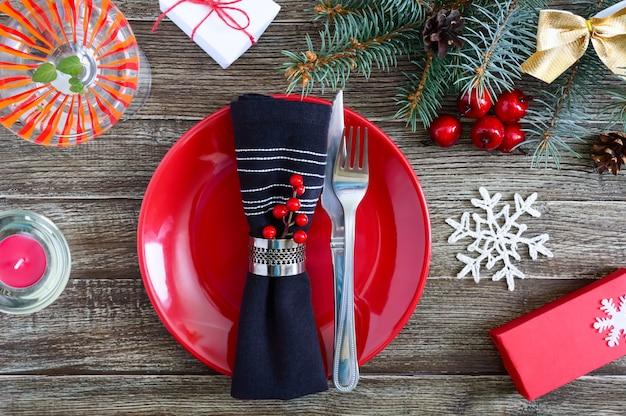 Сервировка рождественского стола. красная тарелка, вилка, нож, бокал для мартини, свеча, салфетка, ветка подарков елки на темном деревянном фоне. скопируйте пространство. рождество рождество новый год праздник фон.