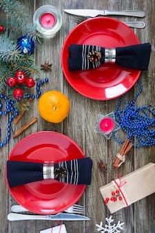 Сервировка рождественского стола. красная тарелка, вилка, нож, мандарины, свеча, салфетка, ветка подарков елки на деревянном фоне. рождество рождество новый год праздник фон.