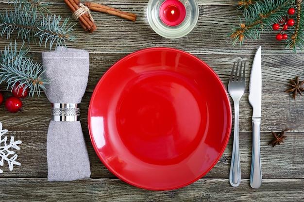 Сервировка рождественского стола. красная тарелка, салфетка, вилка, нож, ветка дерева на деревянном столе. рождество, новогодний праздник фон. вид сверху