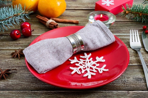 Сервировка рождественского стола. красная тарелка, салфетка, вилка, нож, ветка дерева на деревянном столе. рождество, новогодний праздник фон.