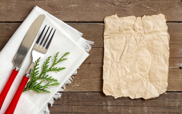 Christmas table setting - white napkin, fork and knife top view with paper on a wooden table