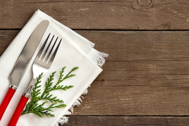Christmas table setting - white napkin, fork and knife top view on a wooden table