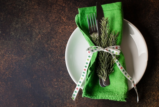 Christmas table setting on white tablecloth over black background