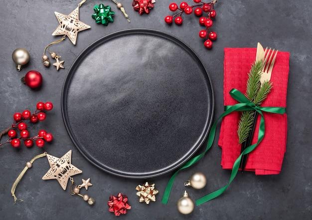 Сервировка рождественского стола с черной керамической пластиной, ветвью ели и золотыми и красными аксессуарами на черном каменном фоне. вид сверху. копировать пространство - изображение