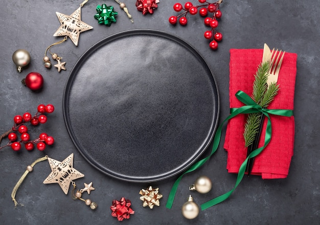 Christmas table setting with black ceramic plate, fir tree branch and gold and red accessories on black stone background. top view. copy space - image