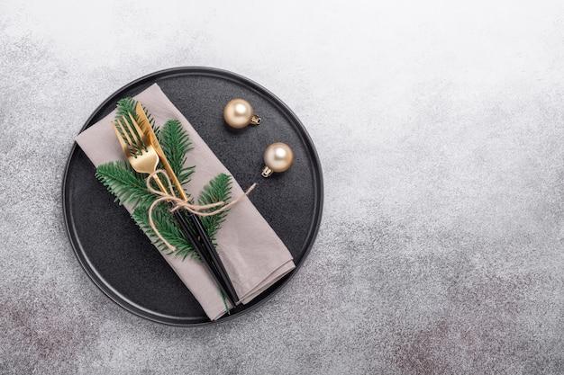 Сервировка стола рождества с черной керамической плитой, подарками и ветвью ели на каменной предпосылке. вид сверху. копировать пространство - изображение
