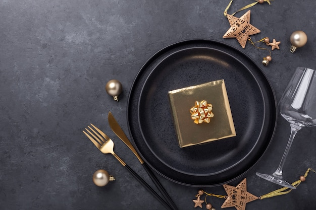 Christmas table setting with black ceramic plate, glass, gift box and gold accessories on black stone background. top view. copy space - image