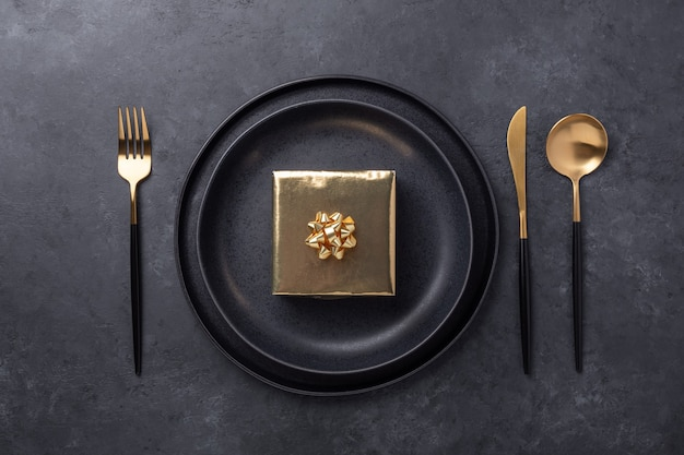 Christmas table setting with black ceramic plate and gold gift box on black stone background. top view - image