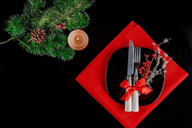 Сервировка стола рождества со свечой и ветвью ели. рождественский обеденный сервиз.