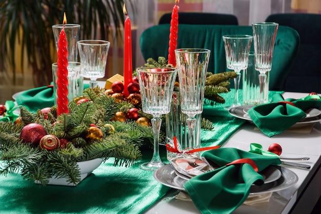 キャンドル、グラス、モミの枝とクリスマステーブルの設定。赤と緑の色でお祝いのテーブルセッティング。