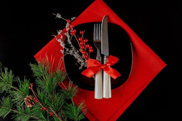 Christmas table setting with decoration on black background.