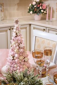 マシュマロで作られたクリスマスツリーの形で装飾されたクリスマステーブルの設定。