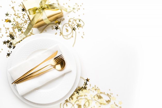 Christmas table setting with dishware, golden silverware on white