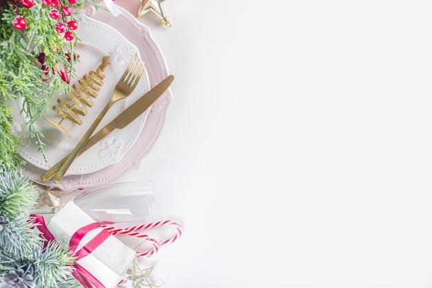 空のプレート、ギフトボックス、クリスマスの装飾が施されたクリスマステーブルセッティング。コピースペース、白い背景と平面図フラットレイ