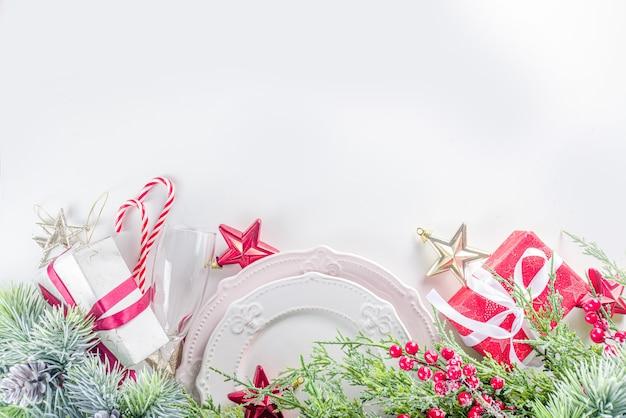 Сервировка рождественского стола с пустыми тарелками, подарочной коробкой и рождественским декором