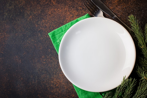 Christmas table setting with festive decorations on white tablecloth over black background