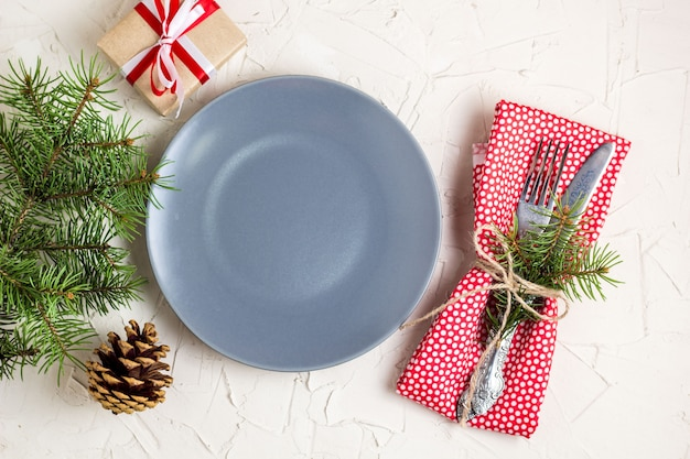 Christmas table setting with gift grey plate on white table. xmas concept top view