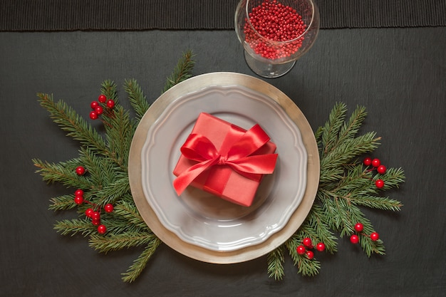 Christmas table setting with gift and red decor on black.
