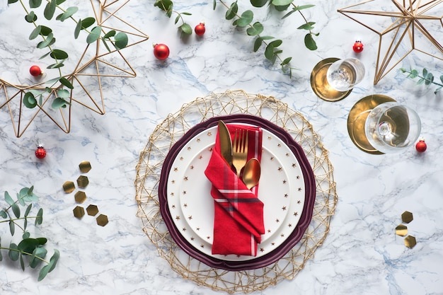 Christmas table setting with gold utensils in folded textile napkin and fresh eucalyptus on marble