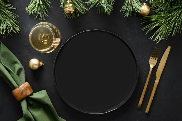 Christmas table setting with golden decoration, cutlery and gold decorations on black background.