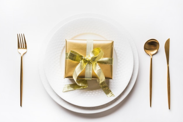 Christmas table setting with golden dishware, silverware on white . top view.