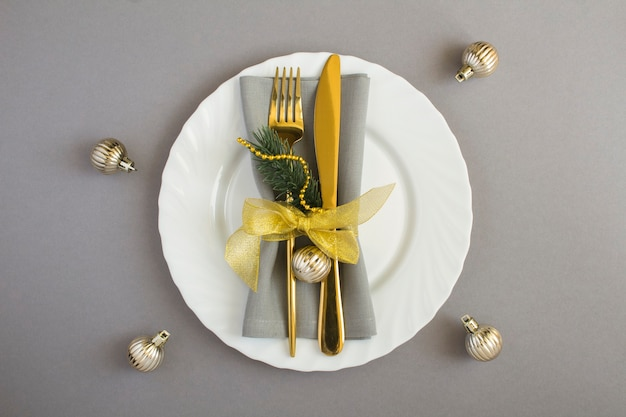 Christmas table setting with gray napkin, gold fork and knifeon the white plate on the gray background. top view. copy space.