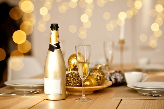 Christmas table setting with holiday decorations in a gold color. new year celebration