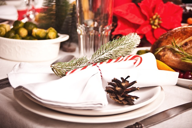 Сервировка рождественского стола с праздничными украшениями. празднование нового года.